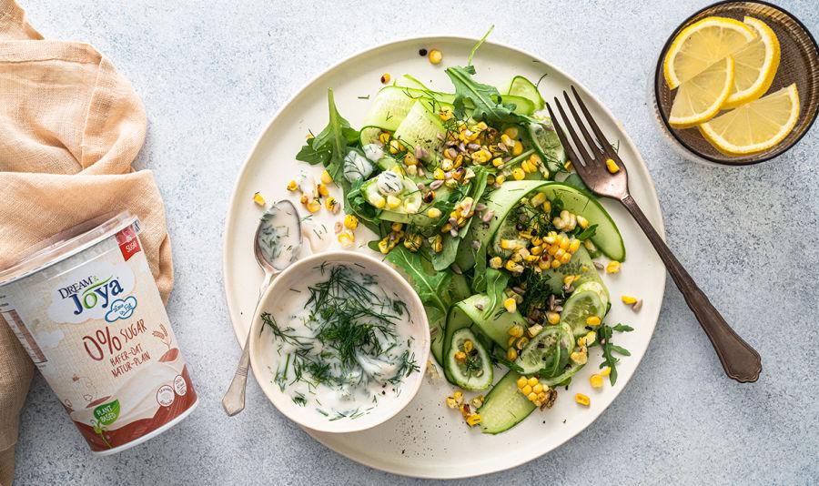 Gurken Mais Grillsalat mit Haferdressing - Auf einem Teller befindet sich ein Salat aus Gurken, Mais und Sonnenblumenkernen, daneben eine Schüssel mit Joghurtdressing und Dille. Im Hintergrund sieht man einen Becher vom Dream & Joya Hafer mit Joghurtkulturen Natur
