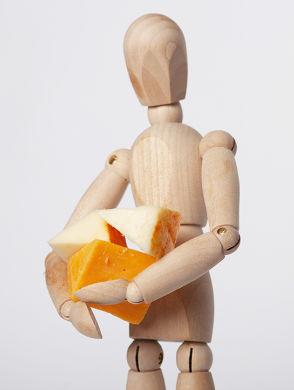 Darmgesundheit TEIL 3 – Milch unter der Lupe - Eine Holzfigur mit zwei Stückchen Apfel und einem Stück Käse vor einem weißem Hintergrund.