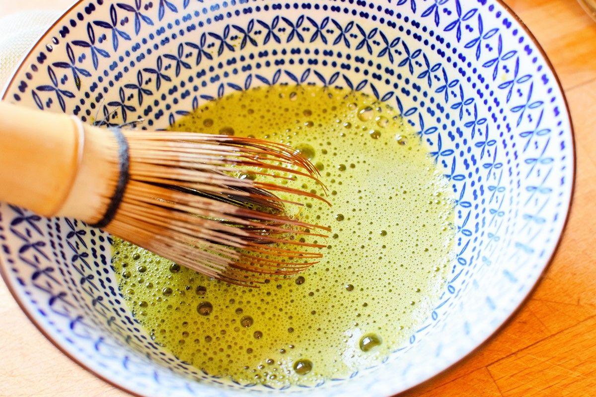 Matcha-Mandel-Shake-Zubereitung - Matcha wird mit einem Matcha-Besen in einer blau-weißen Schale angerührt - © Vegandreams