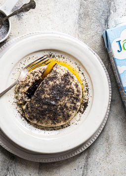 Veganer Germknödel - A yeast dumpling lies in a plate and is sprinkled with liquid margarine and poppy seeds and sugar. Next to it is a pack of Joya Soy Drink Natur