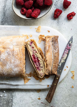 Veganer Himbeer-Topfenstrudel - A curd strudel lies cut on a marbled plate, next to fresh raspberries and a small cup of Dream & Joya with yoghurt cultures.