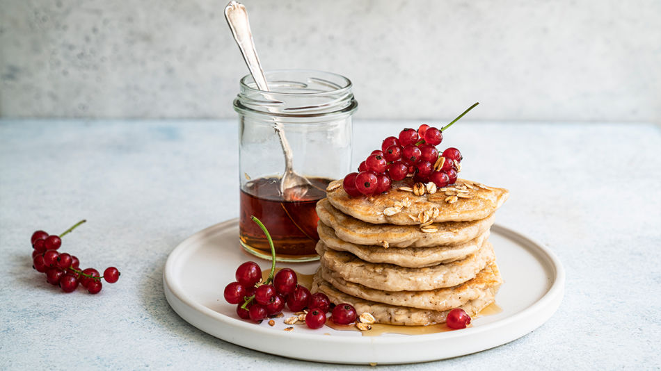 Oat Pancakes - Ein Stapel Pancakes liegt auf einem Teller, darauf sind Ribiseln verstreut. Daneben steht ein Glas mit Ahornsirup