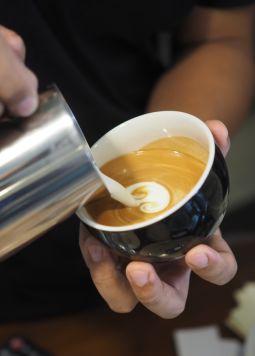Kaffeetrends Joya - Milchschaum wird in eine Tasse Kaffee gegossen - © Shutterstock