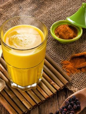 Goldene Milch - Ein glas mit Goldener Milch und verschiedene Gewürze auf einem Holztisch - © Joya