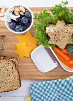 Meal Prepping Ideen - Ein Brett, auf dem Essen zum Mitnehmen in einer Box vorbereitet wird: Brot, Kartotten, Obst und Mandeln. - © Shutterstock