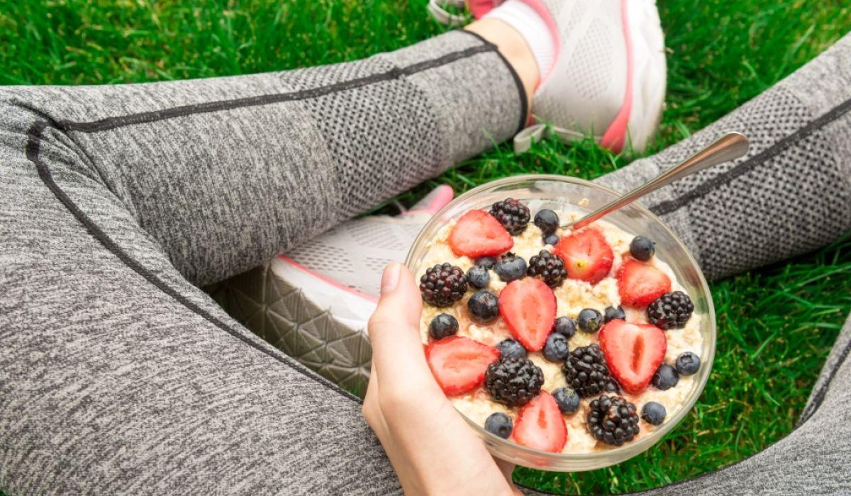Richtig essen rund um die Trainingseinheiten - Eine Frau in Sportschuhen und Sportleggings hält eine Schale mit Müsli und Beeren - © Shutterstock