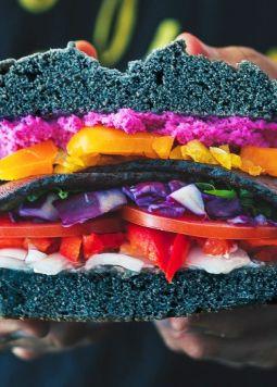 Food Trends  - Zwei Hände halten einen aufgeschnittenen Burger mit vielen Schichten aus buntem Gemüse - © Rustic Vegan on Unsplash