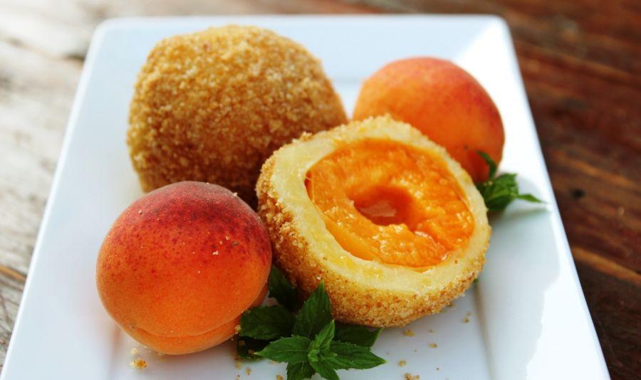 Vegane Marillenknoedel - Zwei vegane Marillenknödel und zwei frische Marillen auf einem einem weißen eckigen Teller - © Shutterstock