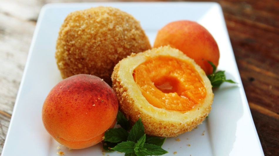 Vegane Marillenknoedel - Two vegan apricot dumplings and two fresh apricots on a white square plate - © Shutterstock