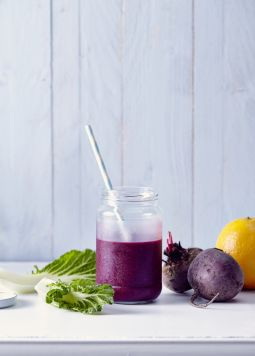 Smoothie with blueberries and red beets - One glass of smoothie with redbeets and an orange