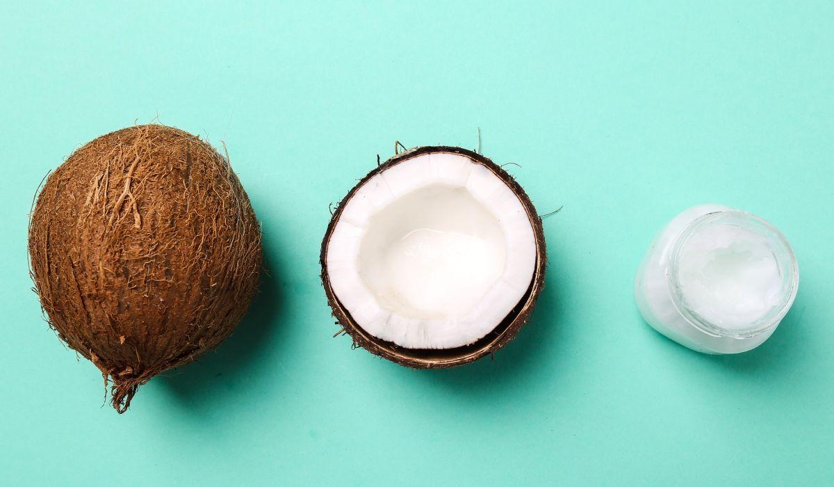 9-erstaunliche-Fakten-ueber-die Kokosnuss - Eine Kokosnuss, eine halbe offene Kokosnuss und ein Glas mit Kokoscreme auf einem türkisen Hintergrund. - © Shutterstock