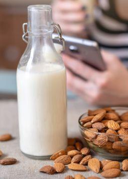Mandeldrink-Mandelmilch-Fruehstueck - Auf einem Tisch liegen Mandeln und es steht eine Flasche mit Mandelmilch. Im Hintergrund sieht man eine Frau mit Smartphone. - © Shutterstock