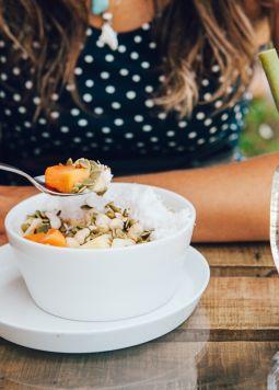 beim-Fruehstueck-die-Welt-retten - Eine Frau löffelt Müsli und Früchte aus einer Schale, daneben steht ein pinker Smoothie. - © Shutterstock