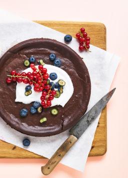 Chocolate Cheesecake - Schokoladen Cheesecake auf einem Holzbrett, garniert mit geschlagener Mandel-Cuisine und frischen Beeren