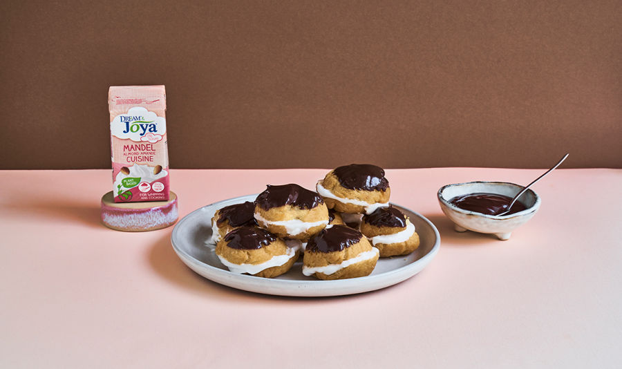 Profiteroles - Profiteroles, mit Schokolade überzogen auf einem Teller. daneben ein Teller mit Schokoladensauce und die Dream & Joya Almond Cuisine