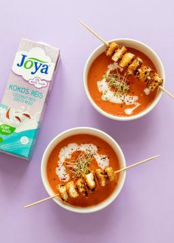 Tomato Red Pepper Suppe - 2 Schüsseln mit Tomaten und roter Paprika Suppe, darauf Tofu-Chili Spieße, daneben eine Packung Kokos Reis Drink, auf lila HIntergrund