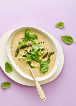 Kokos Spargel Suppe - Kokos Spargel Cremesuppe mit frischen Spargelspitzen und Basilikumblättern. Daneben eine Packung Kokos Drink Protein auf lila Hintergrund.