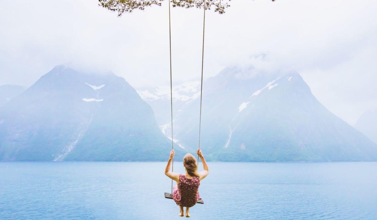 5-alternative-arten-zu-fasten - Eine Frau sitzt auf einer Schaukel und schaut auf einen See und Berge - © Shutterstock